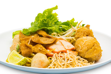 Thai style of dry egg noodle topping with  fried chicken drumstick, bean sprout, red pork, crispy wonton, lemon grass and vegetable