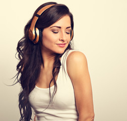 Beautiful happy long hair young woman in casual clothing listening the music in wireless yellow headphone with closed enjoing eyes. Vintage toned portrait