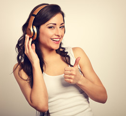 Beautiful happy long hair young woman in casual clothing listening the music in wireless yellow headphone and showing thumb up. Toned portrait