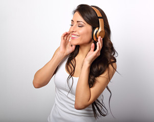 Beautiful happy long hair young woman in casual clothing listening the music in wireless yellow headphone with closed enjoing eyes on white background. Closeup portrait