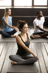 Group of three young sporty afro american and caucasian people sitting in parivritta sukhasana pose, students working out in club with female instructor, indoor, studio