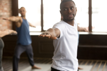 Young smiling black man and a group of sporty people practicing yoga lesson standing in Warrior two exercise, Virabhadrasana 2 pose, working out, indoor close up, studio, focus on fingers