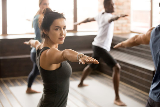 Attractive yogi woman and a group of young sporty people practicing yoga lesson, standing in Warrior two exercise, Virabhadrasana 2 pose, working out, indoor close up, studio