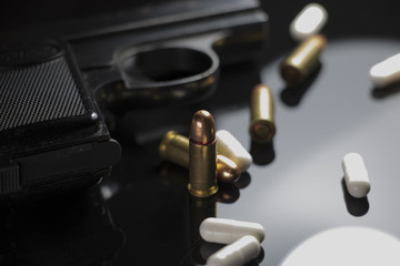 Gun and Bullets on a glass table. Handgun and ammunition.
