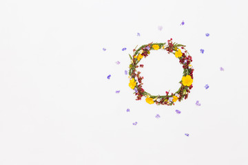 Wreath from summer field flowers on white background with violet flowers around