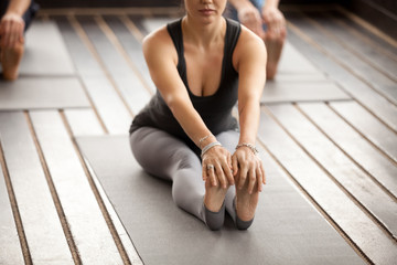 Young sporty woman and a group of people practicing yoga lesson, stretching in paschimottanasana exercise, Seated forward bend pose, working out, indoor close up, studio. Healthy lifestyle concept