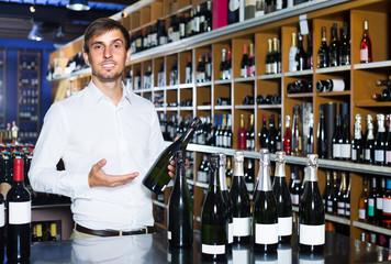 portrait of glad male customer taking bottle of wine in store