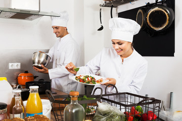 Female chef preparing fresh salad