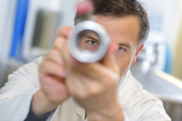 View of male scientist through metal tube