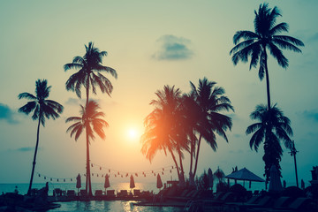 Silhouettes of palm trees on a tropical sea beach during amazing sunset.