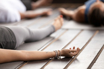 Group of young sporty people practicing yoga, lying in Corpse pose, Savasana exercise, working out, resting after practice, female hand with wrist bracelets close up, studio. Healthy lifestyle concept Wall mural