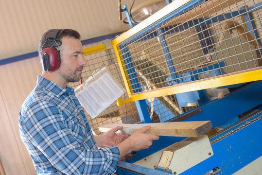 Man putting wood into machine