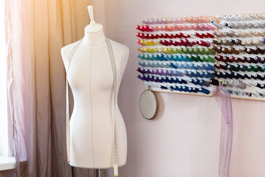 Designer workplace with sew manikins, coils with threads and tape measure.