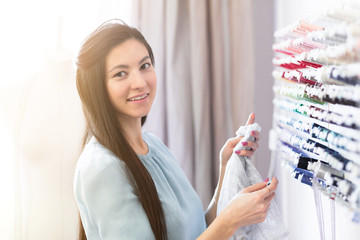 Young seamstress selects threads for making a beautiful fashionable clothes. Designer work place, small business or startup. Light textile industry, creative moments concept