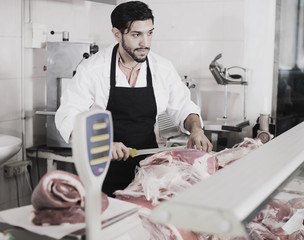 Joyful butcher is cutting meat for clients