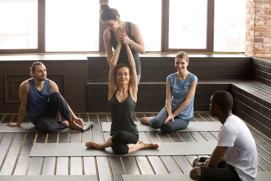 Female instructor helping woman to stretch teaching flexibility in cow face gomukhasana pose at group training with multiracial people in gym studio, yoga teacher assisting in doing fitness exercises