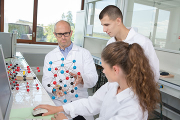 interns in the lab with atoms model