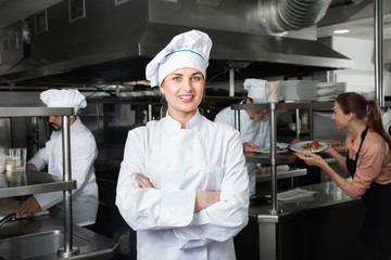 Portrait of young confident woman chef in kitchen of restaurant
