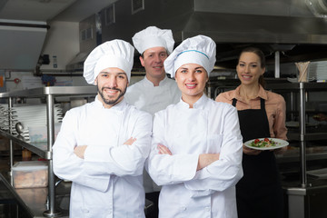 Two chefs in kitchen with staff