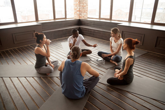 African american yoga instructor talking to diverse group sitting on mat in studio, multiracial happy people having conversation about healthy mindful life and motivation at training seminar class
