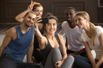 Sporty young fit smiling multi-ethnic people having fun taking group selfie in gym, diverse happy black and white friends making photo on smartphone together sitting in yoga studio at training break
