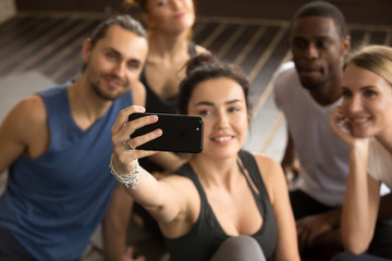 Taking selfie on smartphone concept, sporty woman holding cell shooting video or making diverse friends group self-portrait photo on modern smartphone camera at training break in gym, focus on phone