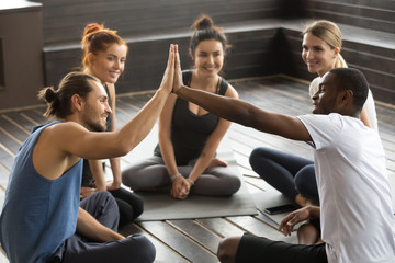 Smiling diverse yoga team members giving high five at group class, fit sporty young african and caucasian men join hands happy to train together supporting encouraging motivation for fitness teamwork