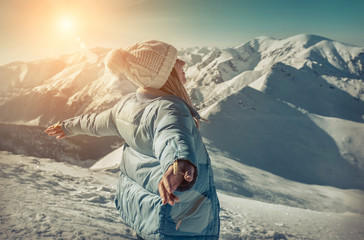 Happy woman relaxing on the top of mountain under blue sky with