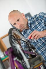man fixing a bicycle