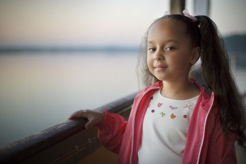 Portrait of girl standing near railing on boat during sunset