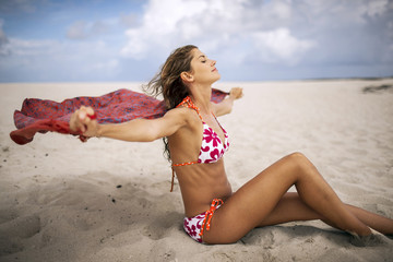 Happy young woman sitting on a beach with her arms outstretched.