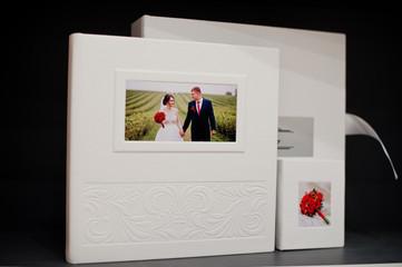 Elegant white or beige photobook, photoalbum and a flash drive case on black background.