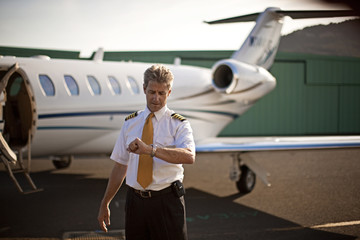 A pilot looking at his watch while standing in front of a private jet