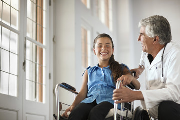 Young girl in a wheelchair talking to her doctor.