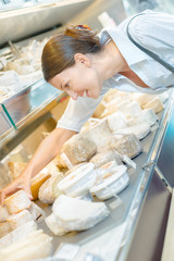 lady choosing cheese from counter