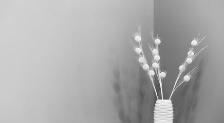 Wazon z ozdobnymi białymi gałązkami na tle szarej ściany.