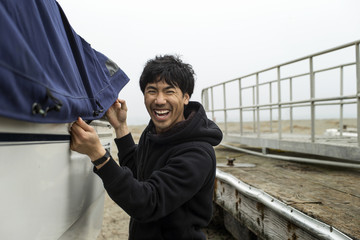 Happy mid adult man protecting his boat with a cover.