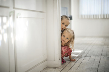 Two sisters crouching behind wall in hallway
