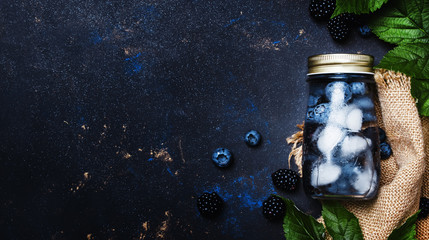 Summer berry drink in bottle with blueberries, blackberries and ice, top view