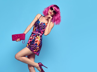 Wall Mural - Gorgeous Fashion woman with Pink Hair, Trendy Sunglasses. Young female model in Stylish Spring Outfit Posing in Studio. Glamour Beautiful Lady. Party fashionable Hairstyle