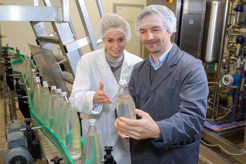 Quality control looking at bottle on production line