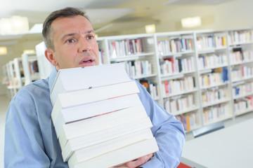 businessman struggling holding many books wish to be promoted