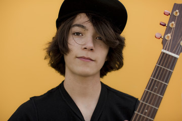 Portrait of boy with guitar standing against yellow background