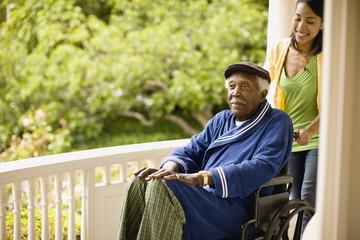Smiling woman pushes a senior man in a wheelchair along a porch.