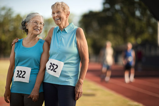 Portrait of happy senior woman standing on an athletic track.