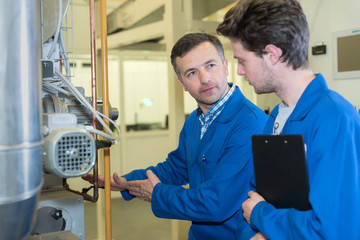 engineer explaining machinery to apprentice