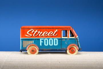 Street food, vintage tin toy truck on blue background.
