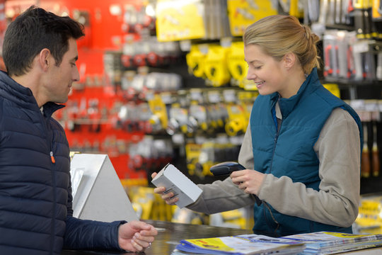 female hardware store seller scanning clients item