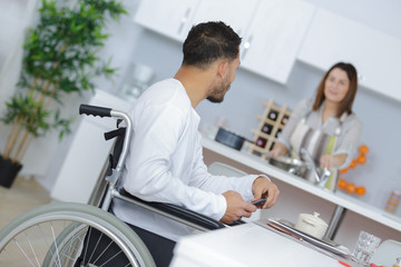 Man in wheelchair talking to partner who is preparing meal