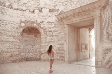 Girl tourist enjoying sightseeing interior door vestibule of the Diocletian's palace in old city center of town Split, Croatia.  Ancient roman landmark.